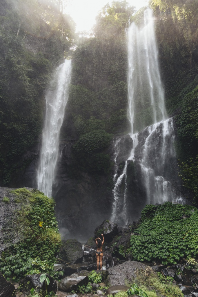 girl standing under Sekumpul Waterfall, Bali