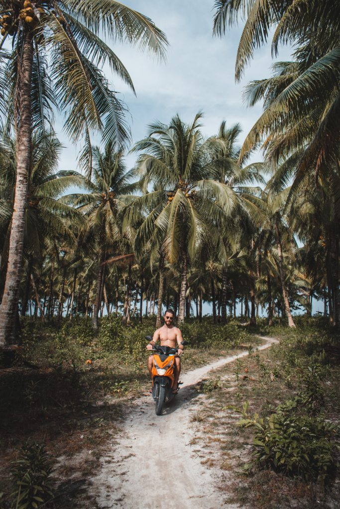 Motorbiking through Siargao island with palm trees