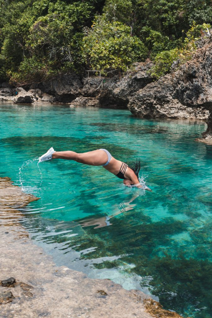 girl diving into magpupungko pools on siargao