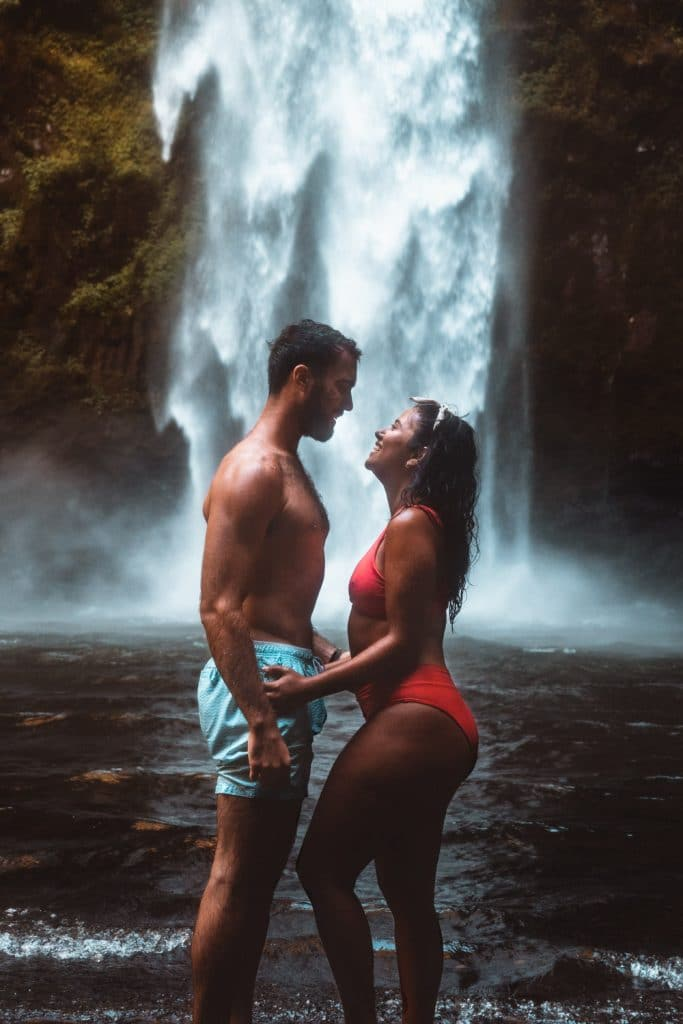 couple posing in front of nungnung the best waterfall in bali
