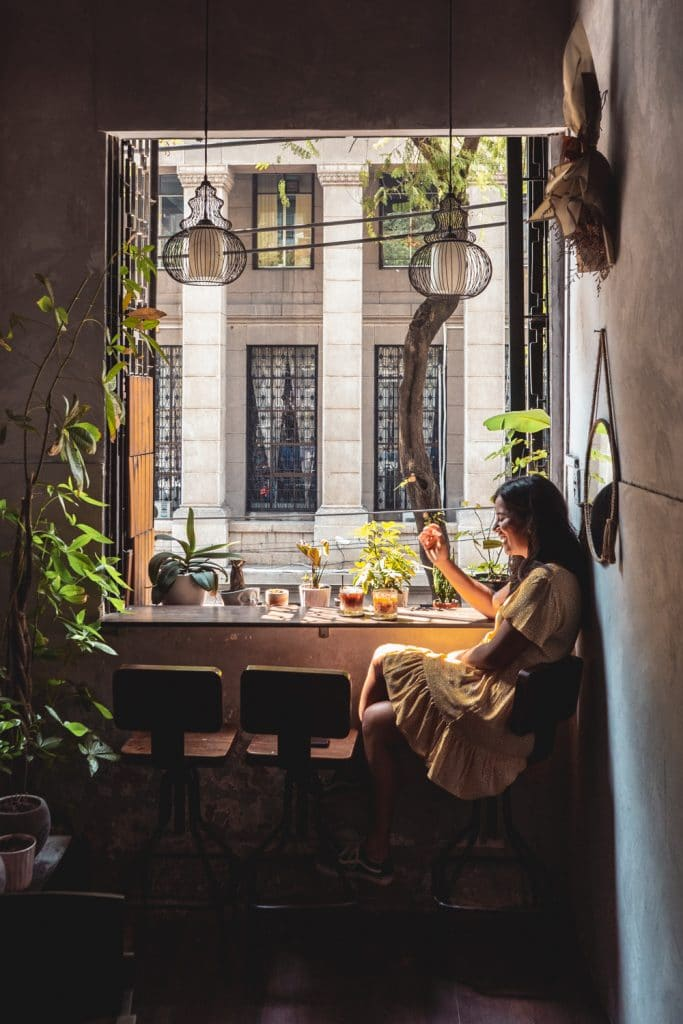 girl sitting next to a window enjoying the best coffee in saigon coffee at whisfee cafe